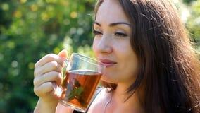 La giovane donna sta bevendo il tè con la menta all'aperto stock footage