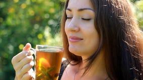 La giovane donna sta bevendo il tè con la menta in natura stock footage