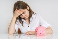 La giovane donna sta calcolando il suo risparmio nella banca dei soldi di porcellino Fotografia Stock Libera da Diritti