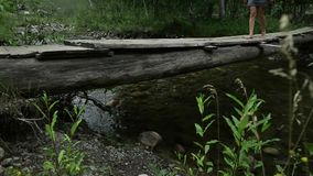 La giovane donna sta camminando lungo un ponte di legno stretto sopra un fiume della montagna concetto di avventura e di campeggi archivi video