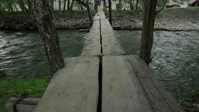 La giovane donna sta camminando lungo un ponte di legno stretto sopra un fiume della montagna concetto di avventura e di campeggi stock footage