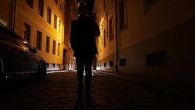 La giovane donna sta camminando tramite le vie scure di vecchia città in Europa Riga, Latvia stock footage