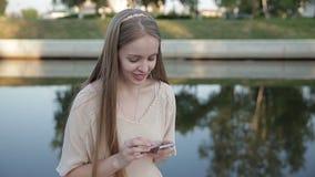 La giovane donna sta controllando il suo smartphone archivi video