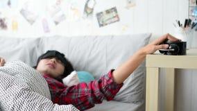 La giovane donna sta dormendo di mattina quando anello il commutatore dell'allarme fuori da e continua a dormire stock footage