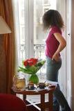 La giovane donna sta ed esamina fuori la finestra la tavola immagine stock libera da diritti