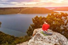 La giovane donna sta facendo gli esercizi di yoga sulla roccia sopra il bello fiume Fotografia Stock Libera da Diritti