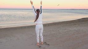 La giovane donna sta facendo gli esercizi per ristabilire la respirazione sulla spiaggia di sabbia all'alba in autunno stock footage