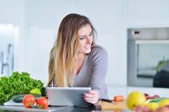 La giovane donna sta facendo l'acquisto online dal computer della compressa La casalinga ha trovato la nuova ricetta per la cottu fotografie stock libere da diritti