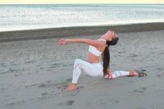La giovane donna sta facendo l'alta posa del pranzo di yoga sulla spiaggia di sabbia all'alba in autunno fotografia stock