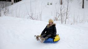 La giovane donna sta facendo scorrere dalla collina della neve a tubatura al rallentatore archivi video