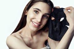 La giovane donna sta facendo una maschera del nero del fronte di bellezza a cary su pelle Fotografia Stock Libera da Diritti