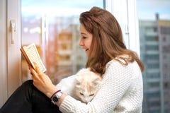 La giovane donna sta leggendo un libro con il suo gatto fotografia stock libera da diritti