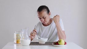 La giovane donna sta mangiando i fiocchi di granturco con latte per la prima colazione con appetito stock footage