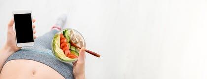 La giovane donna sta mangiando un'insalata e sta usando una forma fisica app sul suo smartphone dopo un allenamento Fotografie Stock Libere da Diritti
