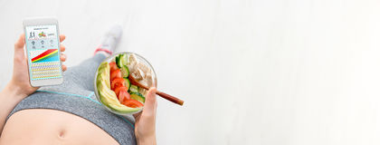 La giovane donna sta mangiando un'insalata e sta usando una forma fisica app sul suo smartphone dopo un allenamento Fotografie Stock
