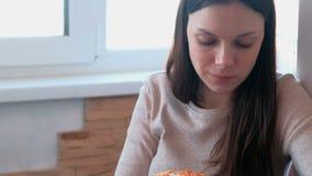 La giovane donna sta mangiando una fetta di pizza casalinga stock footage