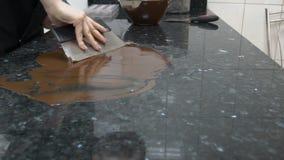 La giovane donna sta mettendo lo strato di cioccolato sul piano d'appoggio in cucina video d archivio