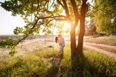 La giovane donna sta oscillando su un'oscillazione in collage della foresta dell'estate Fotografia Stock