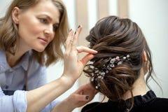 La giovane donna sta ottenendo un taglio di capelli ad un salone immagini stock