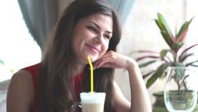 La giovane donna sta parlando a qualcuno in un caffè ed in un latte bevente video d archivio