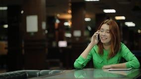 La giovane donna sta parlando sul telefono cellulare che si siede alla tavola nel caffè che tocca i suoi capelli rossi sciolti stock footage