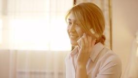 La giovane donna sta parlando sullo smartphone e sul sorridere archivi video