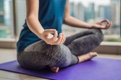 La giovane donna sta praticando l'yoga di mattina sul suo spirito del balcone Fotografie Stock