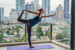 La giovane donna sta praticando l'yoga di mattina sul suo spirito del balcone Fotografia Stock