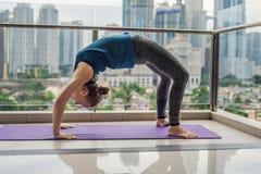 La giovane donna sta praticando l'yoga di mattina sul suo spirito del balcone Immagini Stock