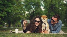 La giovane donna sta prendendo il selfie nel parco che si trova sull'erba con il suo ragazzo ed il cane di animale domestico, ani video d archivio