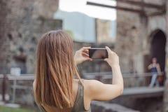 La giovane donna sta prendendo un'immagine di un castello immagini stock libere da diritti