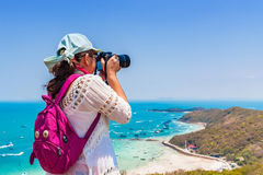 La giovane donna sta prendendo una foto della spiaggia alla cima dell'isola Fotografie Stock Libere da Diritti
