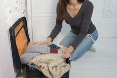 La giovane donna sta raccogliendo una valigia Il viaggiatore che prepara per il viaggio, vista di prospettiva personale quello pr immagini stock libere da diritti