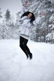 La giovane donna sta saltando nella foresta dell'inverno Fotografia Stock