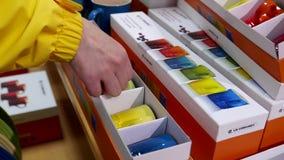 La giovane donna sta scegliendo le tazze nella sezione degli utensili video d archivio