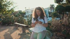 La giovane donna sta sedendosi sul banco in giardino nella sera, giocante con il telefono cellulare video d archivio