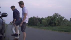 La giovane donna sta sedendosi vicino agli uomini rotti dell'automobile due è venuto ad aiutare la ragazza a riparare la difficol stock footage