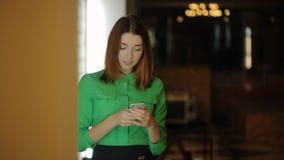 La giovane donna sta stando lavorante con il cellulare e poi lasciante il corridoio del caffè stock footage