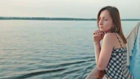 La giovane donna sta sulla piattaforma della nave da crociera archivi video