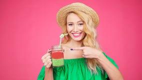 La giovane donna sta tenendo un vetro con il frullato su un fondo rosa archivi video