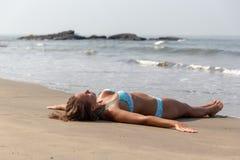 La giovane donna sta trovandosi sulla spiaggia contro lo sfondo del mare e delle pietre fotografia stock
