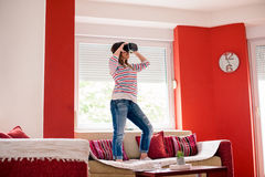 La giovane donna sta usando VR googla a sua casa fotografie stock libere da diritti