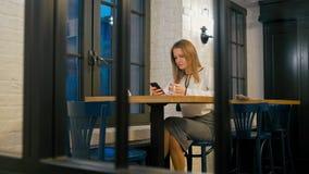 La giovane donna sta utilizzando il App del telefono ed il caffè bevente in ristorante nella sera archivi video