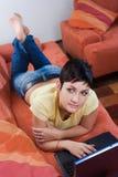 La giovane donna sta utilizzando un computer portatile Immagine Stock