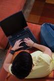 La giovane donna sta utilizzando un computer portatile Fotografia Stock