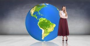 La giovane donna sta vicino alla grande palla della terra Fotografia Stock