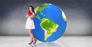 La giovane donna sta vicino alla grande palla della terra Fotografie Stock Libere da Diritti