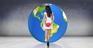 La giovane donna sta vicino alla grande palla della terra Fotografia Stock Libera da Diritti