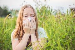 La giovane donna starnutisce a causa di un'allergia all'ambrosia Fotografia Stock