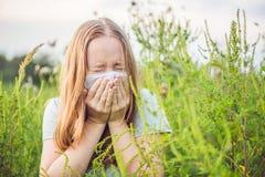 La giovane donna starnutisce a causa di un'allergia all'ambrosia Fotografie Stock Libere da Diritti